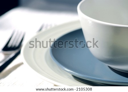 Dinner place setting with plates and soup bowl