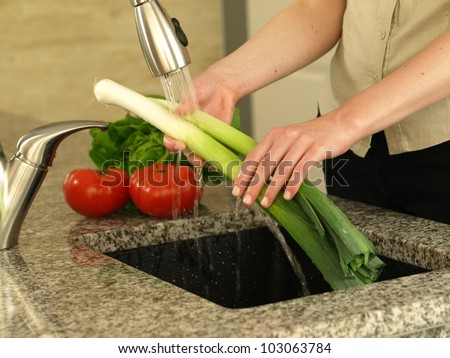 Dinner preparation and woman's hands washing vegetables