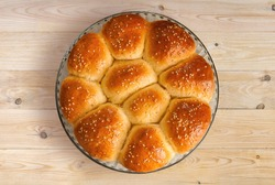 Dinner Roll Placed on Wooden Top  Freshly homemade soft dinner roll, generously sprinkled with sesame seeds, baked on a round glass baking pan sits on a wooden background.