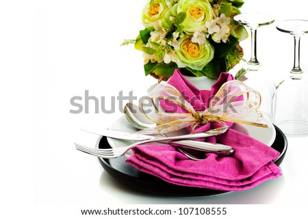 Dinner set with pink napkin and flower on white background as a studio shot