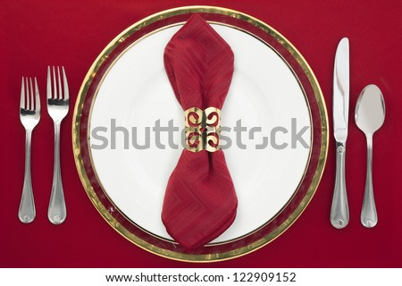 Dinner setting with silverware, red napkin and white plate