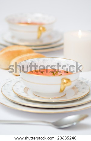 Dinner table set with tomato soup hors d'oeuvre