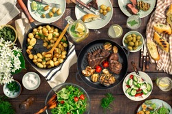 Dinner table with meat grill, roast new potatoes, vegetables, salads, sauces, snacks and lemonade, top view