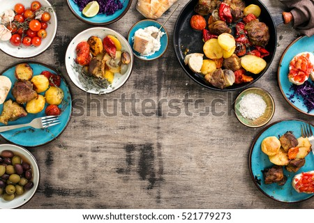 Dinner table with variety food, fried meat with vegetables in a pan, salad and snacks, top view