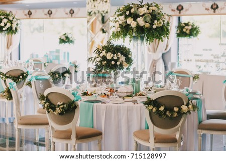 Dinner tables with mint clothes decorated with white roses