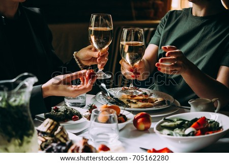 Dinner with friends of family served in a restaurant. Two glasses of white wine in hands #705162280