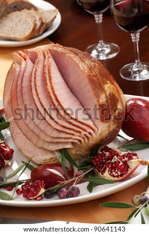 Dinning table set with glazed whole baked sliced ham, garnished with pomegranate, olives, and red pears.