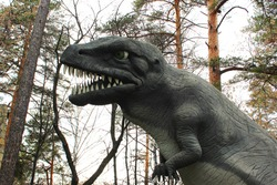 dinosaur figure statues. model dinosaur stands in front of a mossy rock. Close up - huge dinosaur in real size outdoors