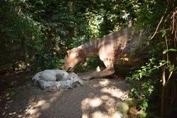 Dinosaur statue in the forest park in nature for background. Realistic model of Dinosaur near its nest with eggs. Dinopark in Turkey, Goynuk. Dinosaur model Maiasaura with a clutch of eggs