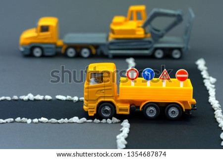 Diorama road construction with yellow construction machinery models. Truck with traffic signs on tipper. Construction concept. Children's toys of construction machinery.