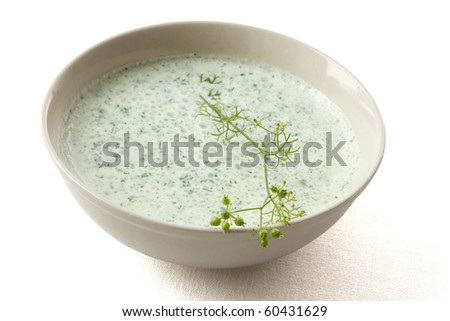 Dip made from yoghurt and herbs with white background and shadow.