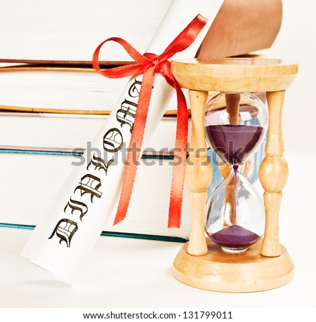 Diploma and books and hourglass