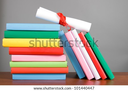 Diploma and stack of books on a gray background