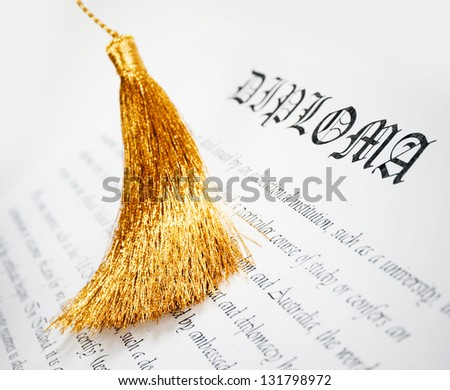 diploma with golden tassel from Graduation hat - stock photo