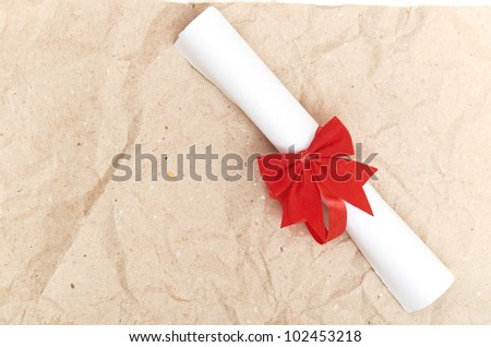 Diploma with red ribbon on old paper - stock photo