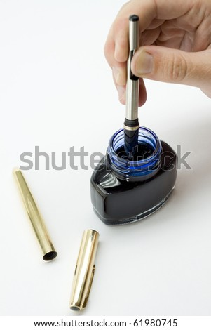 Dipping a gold pen in an ink well - stock photo