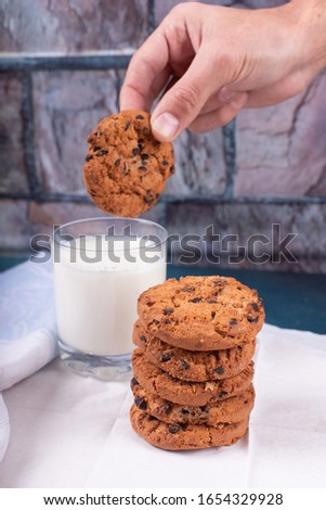 Dipping oatmeal cookies with chocolate chips into milk