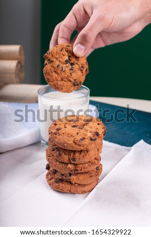 Dipping oatmeal cookies with chocolate chips into milk by hand