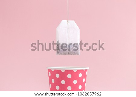Dipping tea bag into paper cup polka design on pastel pink background minimal creative concept.