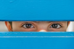direct look of a child between the blue wooden planks