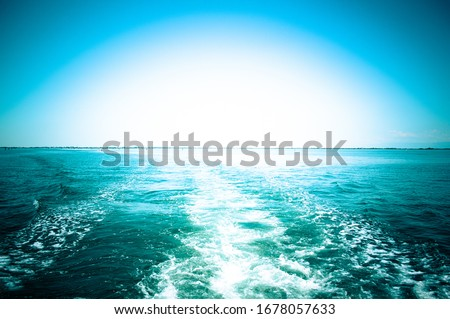 Direct trail of the ship on the high seas against the backdrop of sunrise close up stock photo
