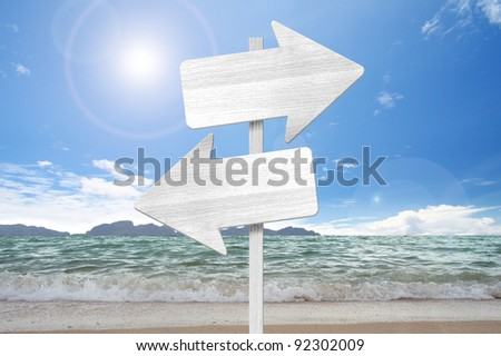 direction arrow wooden  sign on beach