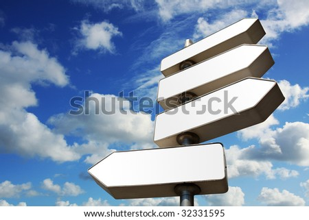 Direction signs with cloudy blue sky in background