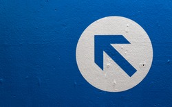 Directional arrow on a blue wall pointing upwards and left.