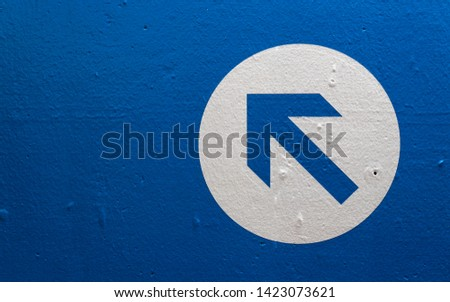 Directional arrow on a blue wall pointing upwards and left. #1423073621