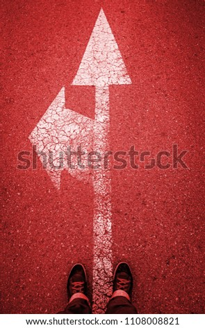 Directional arrow on the asphalt with a few feet, detail of a direction sign painted on the asphalt road safety #1108008821