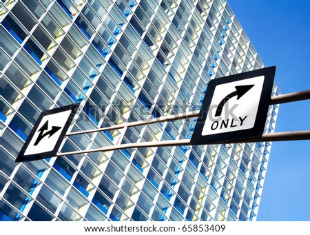 Directional arrow road signs against a glass office building.