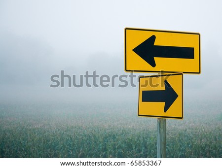 Directional arrow road signs pointing in different directions in the middle of the fog and haze.