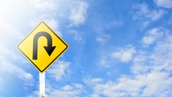 Directional arrow, U-turn sign isolated on cloudy bluesky with clipping paths.
