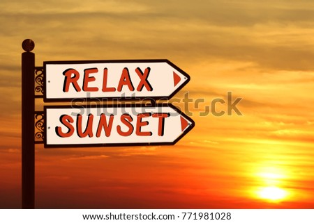 Directional road signs against sunset magic sky. White metal arrows with words RELAX and SUNSET on the signpost #771981028