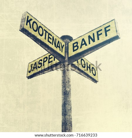 Directional road signs. Signpost. Marker with yellow metal plates pointing direction to Canadian National Parks - Kootenay, Banff, Jasper, Yoho. Tourism and travel. Warm tone. Vintage style #716639233