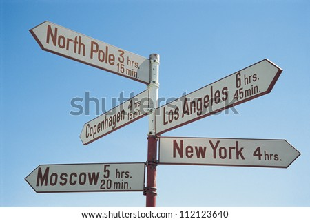 Directions sign post against blue sky