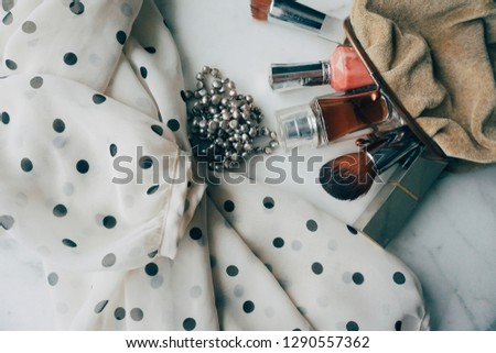 Directly above of a polkadotted blouse in black and white together with a diversity of beauty products in a velvet purse and a pearl jewelry, on marble background