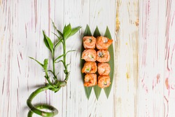 Directly above of Delicious Japanese seafood sushi roll with salmon tataki and roasted black tiger shrimps on top served on bamboo leaves. Bamboo plant near dish on light colorful wooden background