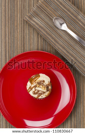 Directly above photograph of a cupcake on a red plate.