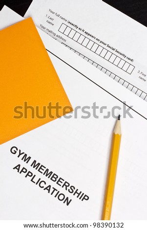 Directly above photograph of a gym application and an orange pencil.