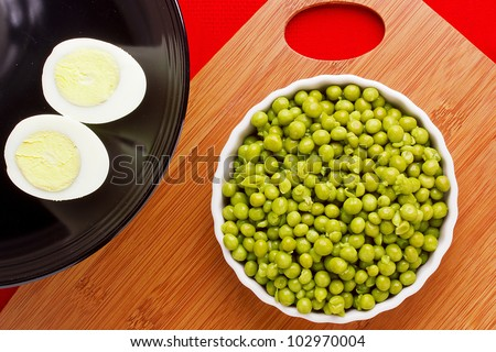 Directly above photograph of eggs and a plate of peas.
