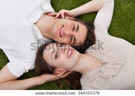 Directly above portrait of loving young couple lying on grass