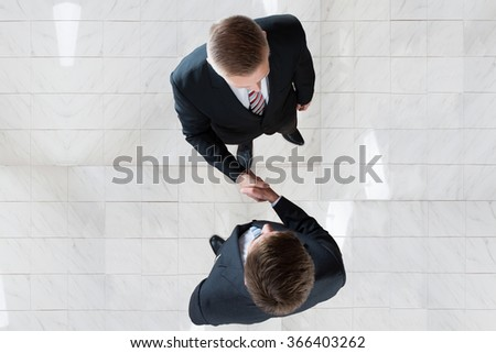 Directly above shot of businessmen shaking hands while standing on tiled floor in office