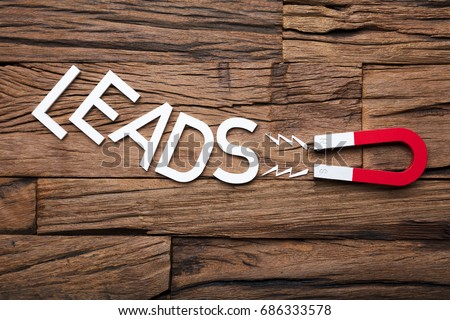 Directly above shot of magnet pulling leads letter blocks on wooden table