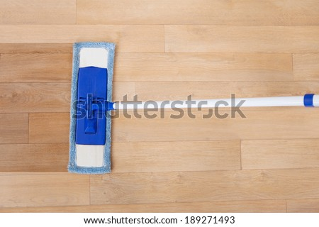 Directly above shot of maid cleaning hardwood floor with mop