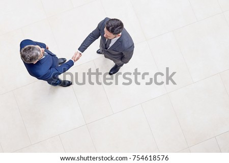 Directly above view of confident business partners in classical suits shaking hands after successful completion of negotiations, interior of office lobby on background