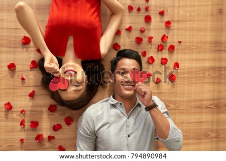 Directly above view of joyful Asian couple lying on floor and covering their eyes with Valentines Day cards, red rose petals scattered everywhere
