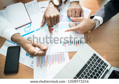 Directly above view of unrecognizable business analysts sitting at table and discussing graphs while analyzing location of sales
