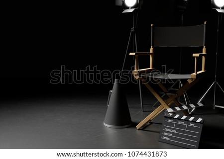 Director Chair,Megaphone,Movie Clapper and lighting equipment on dark background. 3d rendering