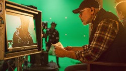 Director Looks at Display and Compares to Storyboard while Shooting Blockbuster Movie. Green Screen Scene with Actor Wearing Motion Caption Suit. Film Studio Professional Crew Doing High Budget Movie